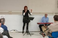 Inquadratura frontale di Lorena mentre canta e suona uno shaker; io sono seduto alla sua sinistra e sto suonando il cajón.