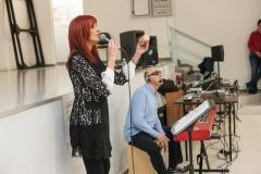 Primo piano di Lorena ripresa di profilo mentre sta cantando; in secondo piano io sono ripreso mentre suono il cajón.