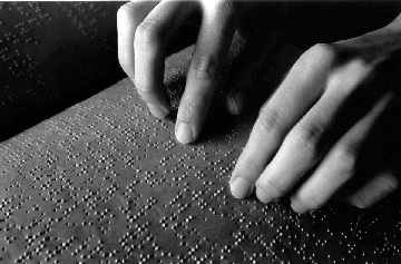 Foto artistica di mani che leggono il codice Braille