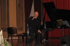 In questa foto sono seduto al pianoforte, ma sono rivolto verso il pubblico ripreso frontalmente.