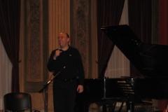 Sono ripreso frontalmente accanto al pianoforte mentre, rivolto verso il pubblico, presento i componenti del gruppo.