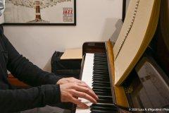 Primo piano di un uomo in nero del quale sono inquadrati la zona delle labbra e del mento coperti dalla mascherina, metà busto esclusa la spalla destra rispetto all'osservatore, , l'avambraccio destro e tutto l'arto superiore sinistro e le mani posate sulla tastiera di un pianoforte a muro nel gesto di suonare. Sul leggio dello strumento si vede un libro braille; Sullo sfondo, compaiono delle custodie di strumenti musicali nere accatastate sotto un pezzo di ciò che si intuisce essere un quadro raffigurante, come si legge da una didascalia dello stesso, l'albero genealogico degli stili e dei massimi esponenti del jazz come si trattasse di una grande famiglia di consanguinei; sotto l'angolo destro del quadro, è visibile un libro chiuso.: foto a colori.