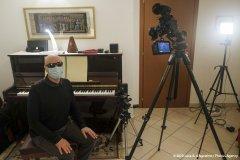 Foto di una stanza allestita per le riprese di un video nella quale si vede un uomo con occhiali scuri e mascherina seduto sul seggiolino del pianoforte a muro; dietro di lui, puntate sul soggetto, si vedono una macchina fotografica, una telecamera e una luce artificiale professionali: foto a colori.