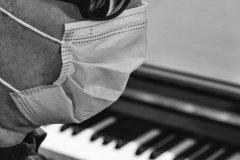 Primo piano del viso ripreso di profilo e di una parte del busto di un uomo con occhiali e mascherina. Sullo sfondo, sfocati, si vedono un pianoforte aperto e un libro appoggiato sul leggio: foto in bianco e nero.