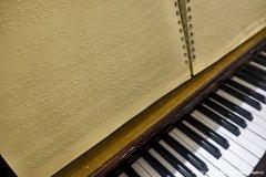 Foto che ricalca quella precedente, ma, l'inquadratura  è un po' più abbassata poiché è visibile un maggior numero di tasti del pianoforte e, del libro,  compare solamente la metà inferiore: foto a colori.