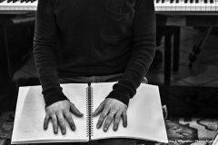 Primo piano di mani maschili posate su un libro braille aperto sulle ginocchia; si intravede il busto fino all'altezza del petto; dai fianchi in su e dietro il soggetto inquadrato, si vedono un tappeto e un pianoforte nel quale si riflettono le caviglie e i piedi: foto in bianco e nero.