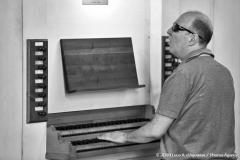 Sono seduto alla console dell'organo ripreso di tre quarti durante le prove prima del concerto.