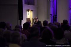 Ripresa del pubblico di spalle; io sono in piedi inquadrato frontalmente mentre presento un brano.