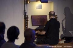 Sono inquadrato di spalle mentre suono; l'ombra di daniele si riflette sul pannello posizionato alla destra dello strumento.