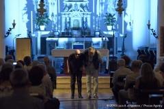 Siamo ripresi mentre ci inchiniamo dopo il concerto con l'altare della chiesa sullo sfondo e le navate occupate dal pubblico.