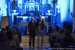 Siamo inquadrati in piedi dopo il concerto con l'altare della chiesa sullo sfondo e le navate occupate dal pubblico.