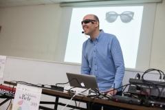 Sono ripreso in piedi davanti al computer mentre illustro agli studenti la prima diapositiva proiettata alle mie spalle: sto sorridendo.