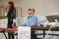 Come nell'immagine precedente, in questa fotografia si vede Lorena con la schiena in posizione leggermente incurvata  mentre io - alla sua sinistra - sto suonando la tastiera; nell'immagine compaiono anche il computer e il manifesto che promuove  l'evento.