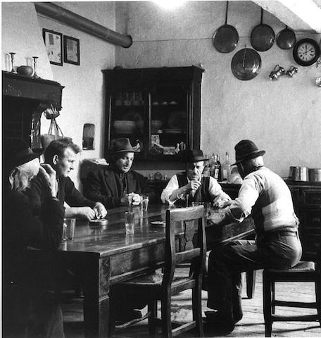Ripresa di un caratteristico interno di un'osteria con persone sedute ad un tavolo
