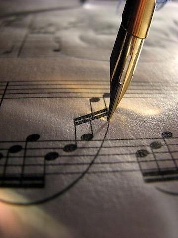 Immagine di una penna stilografica che verga uno spartito musicale