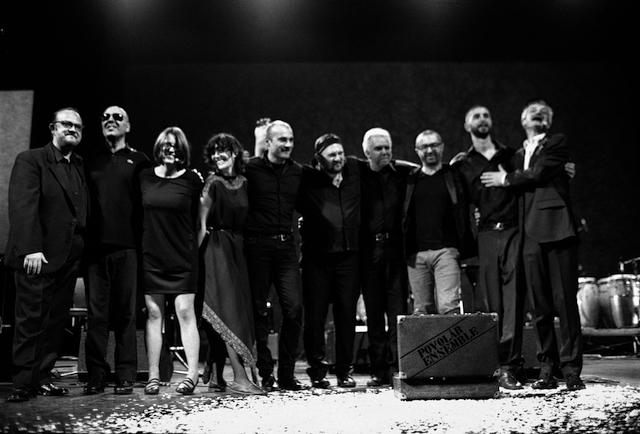Ripresa frontale di attori e musicisti sul palco scenico