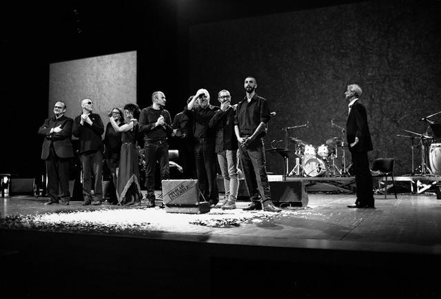 Inquadratura frontale di attori e musicisti sul palco scenico