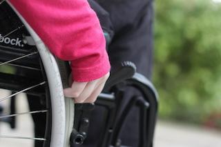 Ripresa del dettaglio ruota di una carrozzina con la mano di un disabile poggiata sul mancorrente
