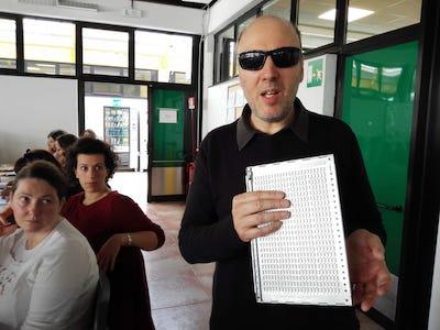 Sono ripreso mentre esamino una pagina Braille