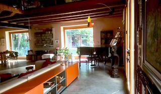 Panoramica del salone con vista dell'abitazione di Francesca e Toni con il pianoforte a coda sullo sfondo