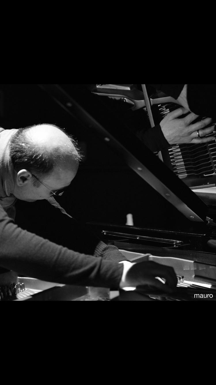 Questa foto mi inquadra dentro la coda di un pianoforte mentre percuoto le corde.