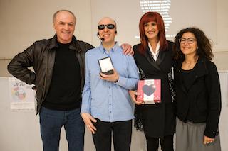 Ho appena ricevuto il premio, alla mia destra c'è il presidente del comitato, alla mia sinistra ci sono Lorena e la referente scolastica dell'iniziativa.