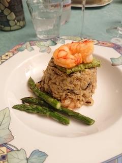 Riso integrale con asparagi e gamberetti, alcuni piccoli asparagi a bordo piatto e alcuni gamberoni guarniscono la pietanza