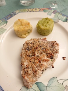 Porzione di pesce spada impanato con semi tritati contornato da piccoli tortini di patate ripieni.