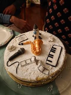 Base di pan di Spagna con farcitura di crema al limoncello; sulla superfice della torta sono adagiati alcuni oggetti in 3D realizzati con pasta di zucchero: un microfono, un sassofono, una tastiera di pianoforte e un missile della NASA.