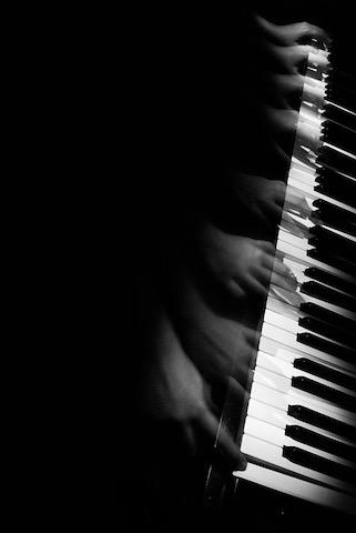Più mani stanno suonando sulla tastiera di un pianoforte.