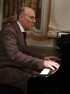 Primo piano del mio mezzo busto ripreso dal lato destro mentre sto suonando un pianoforte grancoda del quale se ne intravede una parte. per la circostanza, indosso giacca e cravatta.