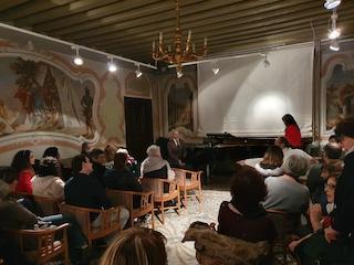 Ripresa del pubblico di spalle. Sullo sfondo si intravede la figura di Lucia all'estremità del pianoforte a coda davanti al quale, sono seduto di tre quarti mentre sto conversando  con i presenti.