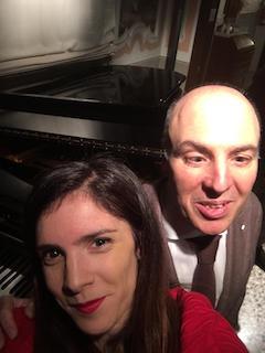 Selfie scattato da Lucia a fine di un concerto tenuto nel periodo natalizio; siamo davanti a un pianoforte a coda; lei è alla mia destra e sorride; io le tengo affettuosamente una mano appoggiata sulla spalla.