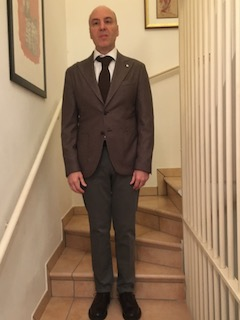 In questa immagine sono inquadrato in abito elegante, ma non formale; indosso giacca e cravatta; sono ripreso in piedi mentre sto scendendo una scala.