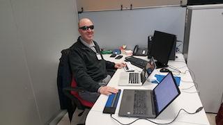 In questa immagine sono seduto alla scrivania del mio ufficio, attorniato da computers e dispositivi elettronici.