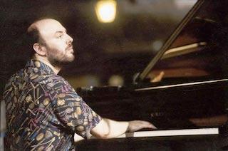 In questa foto di repertorio sono ripreso quasi di spalle; sono seduto al pianoforte, porto la barba e indosso una camicia variopinta.