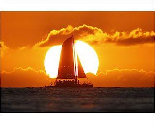 Sullo sfondo un grande sole incorniciato sopra e sotto da nuvole color del fuoco, al centro di esso è visibile la silouette di una barca a vela. Davanti a tutto ciò: primo piano del mare.