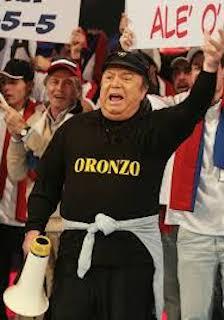 Primo piano di Lino Banfi che indossa una maglia nera con sopra scritto Oronzo in giallo. Nella mano destra un megafono bianco e rosso. Sullo sfondo una folla di persone che applaudono e reggono due cartelli, uno indicante il punteggio e l'altro un incitamento alla propria squadra del cuore.