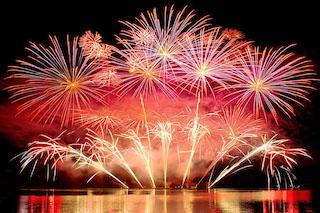 Foto panoramica rappresentante fuochi d'artificio dalle tonalità rosse e viola che, dopo essere esplosi, formano in cielo una sfumatura simile ad un tramonto. Il tutto si riflette su uno specchio d'acqua.