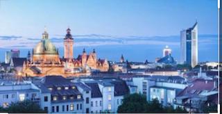 Ripresa panoramica di Lipsia in un contrasto di colori freddi e caldi mentre  le case sono di un delicato blu argentato, una grande chiesa risplende di riflessi dorati e di cupole verde e blu brillante. Sullo sfondo un alto palazzo e delle nuvole indaco che si fondono con il cielo.