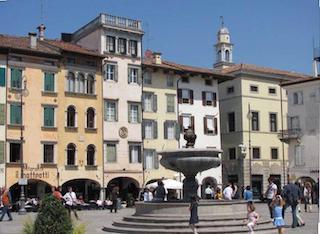 Foto di Piazza San Giacomo, in un tripudio di colori donati dalle case sullo sfondo. Al centro dell'inquadratura una fontana imponente con scalinata attorno alla quale giocano due bambine e molte persone passeggiano. Sempre sullo sfondo, domina la cima di un campanile.