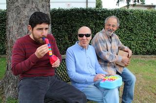 Foto del trio scattata durante un momento ludico trascorso a casa Parisi; siamo seduti su una panchina del giardino mentre suoniamo degli strumenti giocattolo.