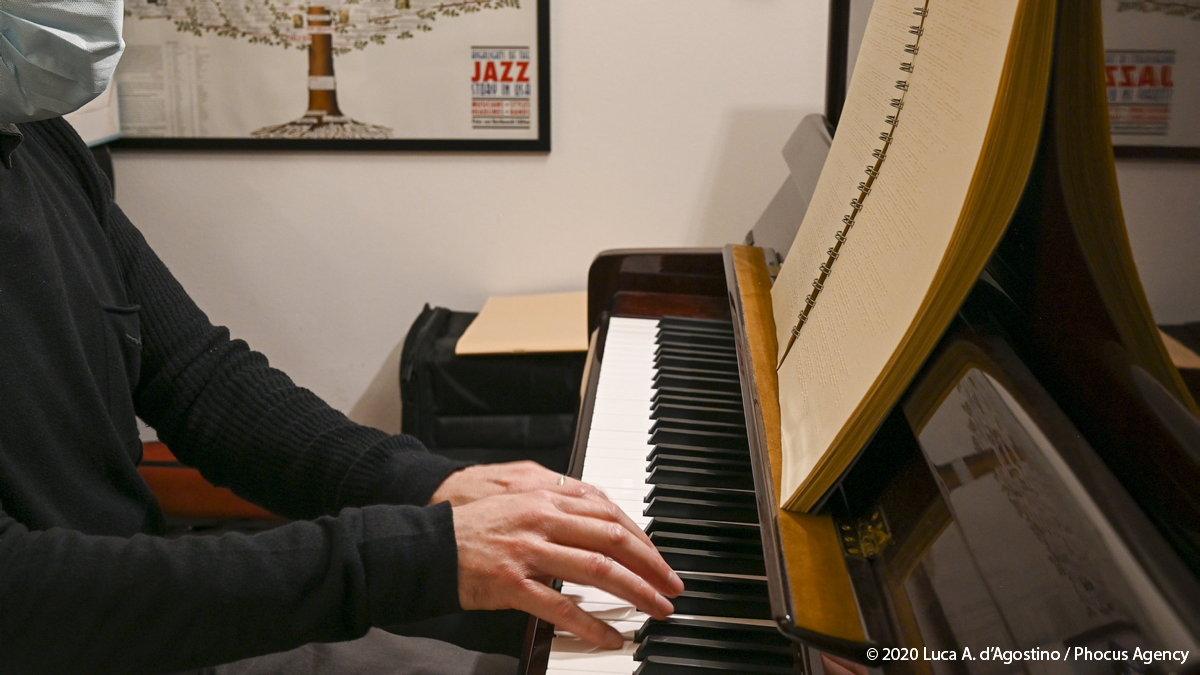 In questa foto sono vestito di nero; l'inquadratura mostra la parte delle labbra e del mento coperti dalla mascherina, metà busto esclusa la spalla destra rispetto all'osservatore, , l'avambraccio destro e tutto l'arto superiore sinistro e le mani posate sulla tastiera di un pianoforte a muro nel gesto di suonare. Sul leggio dello strumento è visibile un libro braille; Sullo sfondo, compaiono delle custodie di strumenti musicali nere accatastate sotto un pezzo di ciò che si intuisce essere un quadro raffigurante, come si legge da una didascalia dello stesso, l'albero genealogico degli stili e dei massimi esponenti del jazz come si trattasse di una grande famiglia di consanguinei; sotto l'angolo destro del quadro, è visibile un libro chiuso.: foto a colori.
