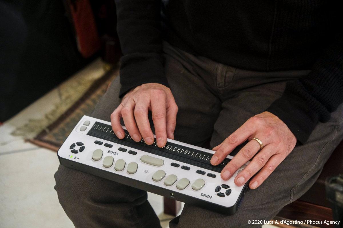 Primo piano delle mie mani posate su un dispositivo per la lettura braille, esso è appoggiato sulle ginocchia; si intravede il busto fino all'altezza del petto; dietro di me è visibile la sagoma sfuocata di un pianoforte: foto a colori.